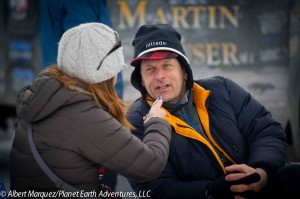 Emily Schwing, KUAC Fairbanks, interviews Martin at the restart. Photo: Albert Marquez/Planet Earth Adventures, LLC