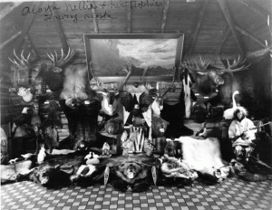 """""""Alaska Nellie (Lawing) wearing a parka and mukluks and holding a gun, as she sits among her animal hunting trophies.""""  [Alaska State Library Fred Henton Collection AMRC-b65-18-741]"""