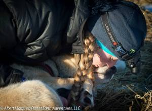 First place musher Kristy Berington gives one of her dogs a kiss. [Photo by Albert Marquez/Planet Earth Adventures]