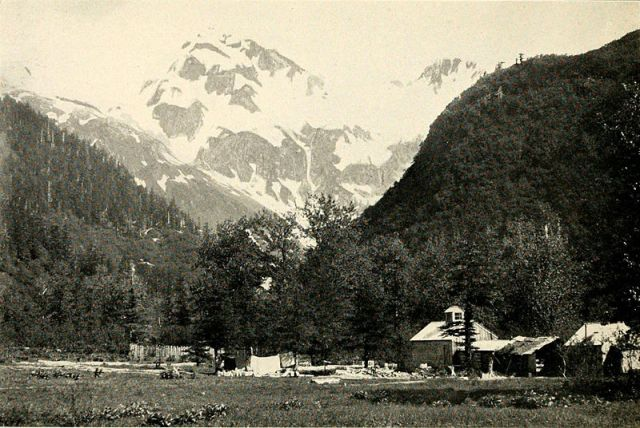 """An Alaskan Road House""; stable, cabins, and tents at the mouth of a mountain valley, a snowy peak framed in the valley. Location not specified. From 'Alaska the Great Country,' copyright 1908, MacMillan Co., by Ella Higginson, photographer E.A. Hegg, Juneau"