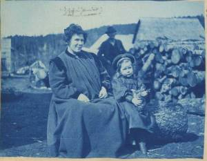 First white child born in Cook Inlet, Martha White, and her mother, left, in Sunrise, Alaska in 1898. The child is wearing a hat and holding a cat. A man, several wooden buildings and a pile of logs are visible in the background. Photograph taken during the 1898 Cook's Inlet Exploring Expedition led by Edwin F. Glenn on behalf of the U.S. Army. The photographer is unidentified. Title taken from caption written on back of photograph. [Edwin F. Glenn papers, Archives and Special Collections, Consortium Library, University of Alaska Anchorage]